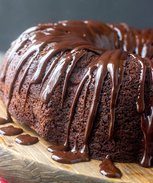 whole chocolate bundt cake with glossy chocolate glaze dripping down the side