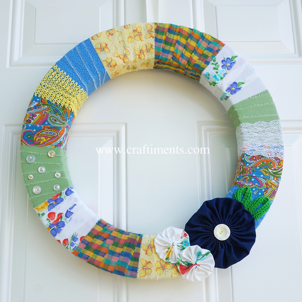 Wreath wrapped with torn fabric strips and yo-yo flowers