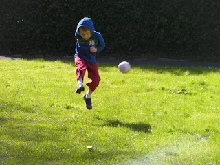 boy kicking football off the ground