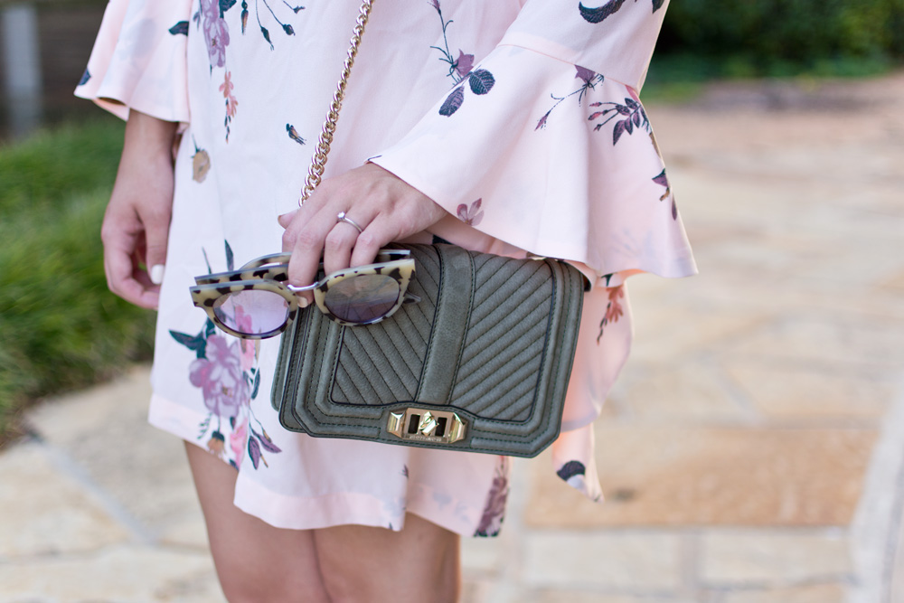 outfit details of floral pink bell sleeve dress with olive green rebecca minkoff bag and tortoiseshell sunglasses