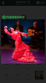 На сцене исполняет танец фламенко женщина в красном платье