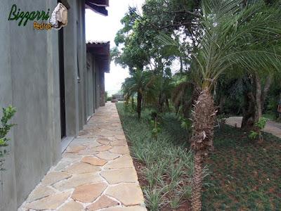 Execução do caminho de pedra Goiás como colocação do pedrisco palha nas juntas da pedra e execução do paisagismo com as gramas preta, as mudas de barba de serpente e mudas de palmeira phoenix em residência em Piracaia-SP.