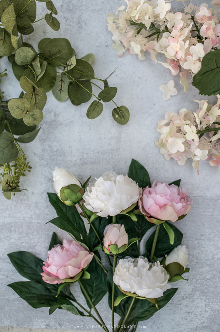 Silk peonies, hydrangea and eucalyptus flowers on cement backdrop