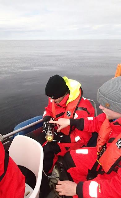 Kaksi pelastuspukuista henkilöä tutkii kameraa veneessä.