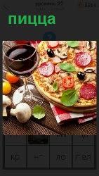 приготовлена пицца с бокалом и овощами рядом