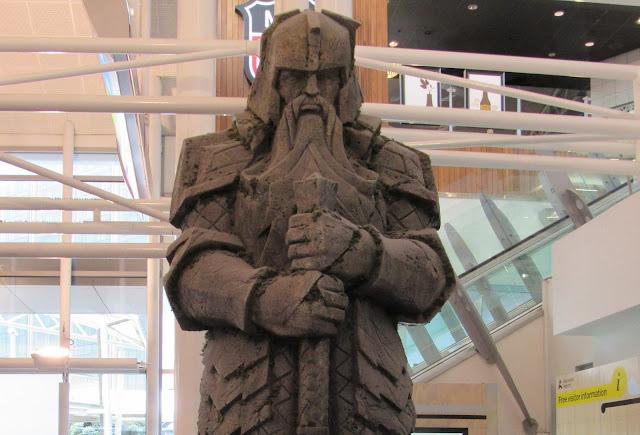 Figura gigante que representa un enano del señor de los anillos y el hobbit en el aeropuerto de Auckland