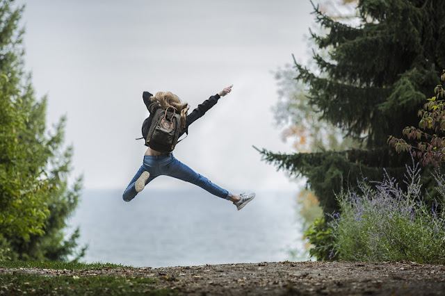 Young girl on a hike, leaping in the air, dynamic
