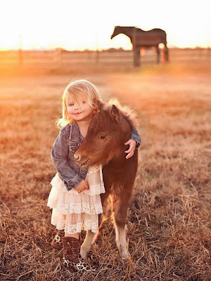 Una niña abrazando un pequeño poni al atardecer.