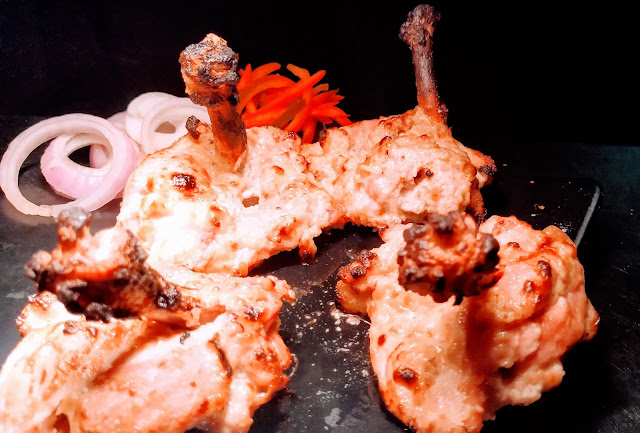 Garnished chicken kalmi kebab pieces with onions food recipe