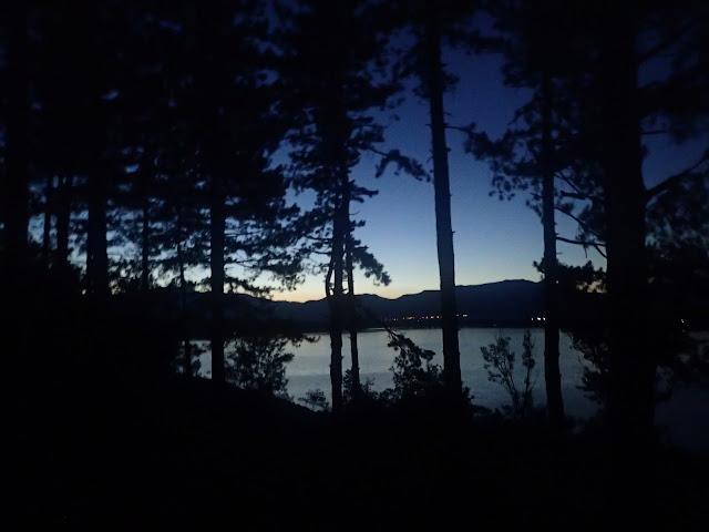 Wieczorny zalew, skryty za drzewami. W oddali majaczy zapora