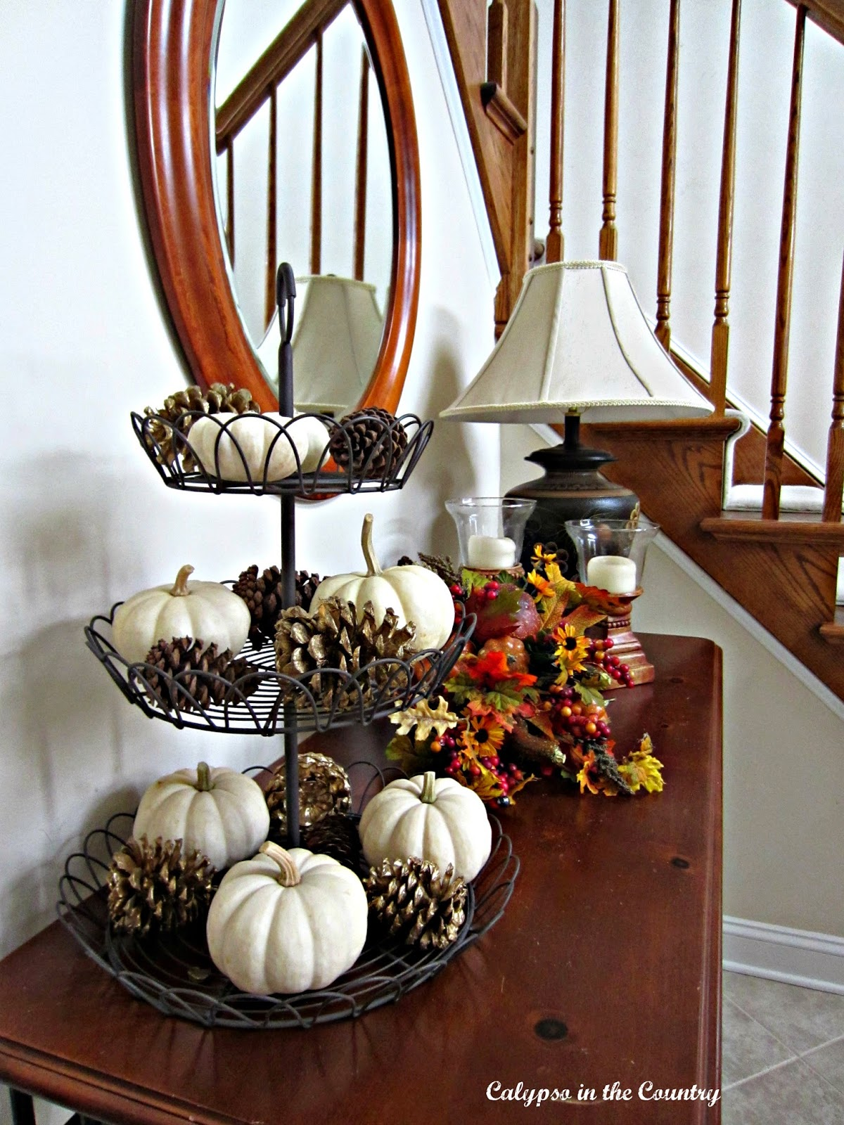 Tiered tray with pumpkins and pine cones