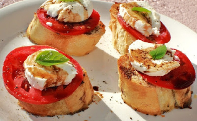 this is a salad on top of bread with cheese and tomato and basil