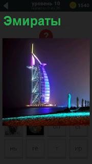 Освещенное здание в Эмиратах, которое стоит в середине водоема в виде паруса яхты