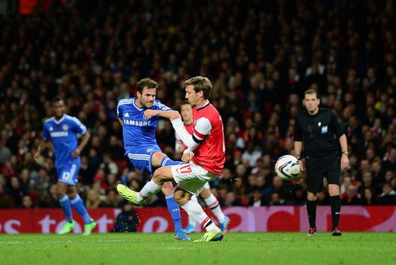 Chelsea player Juan Mata shoots to score his side's second goal against Arsenal