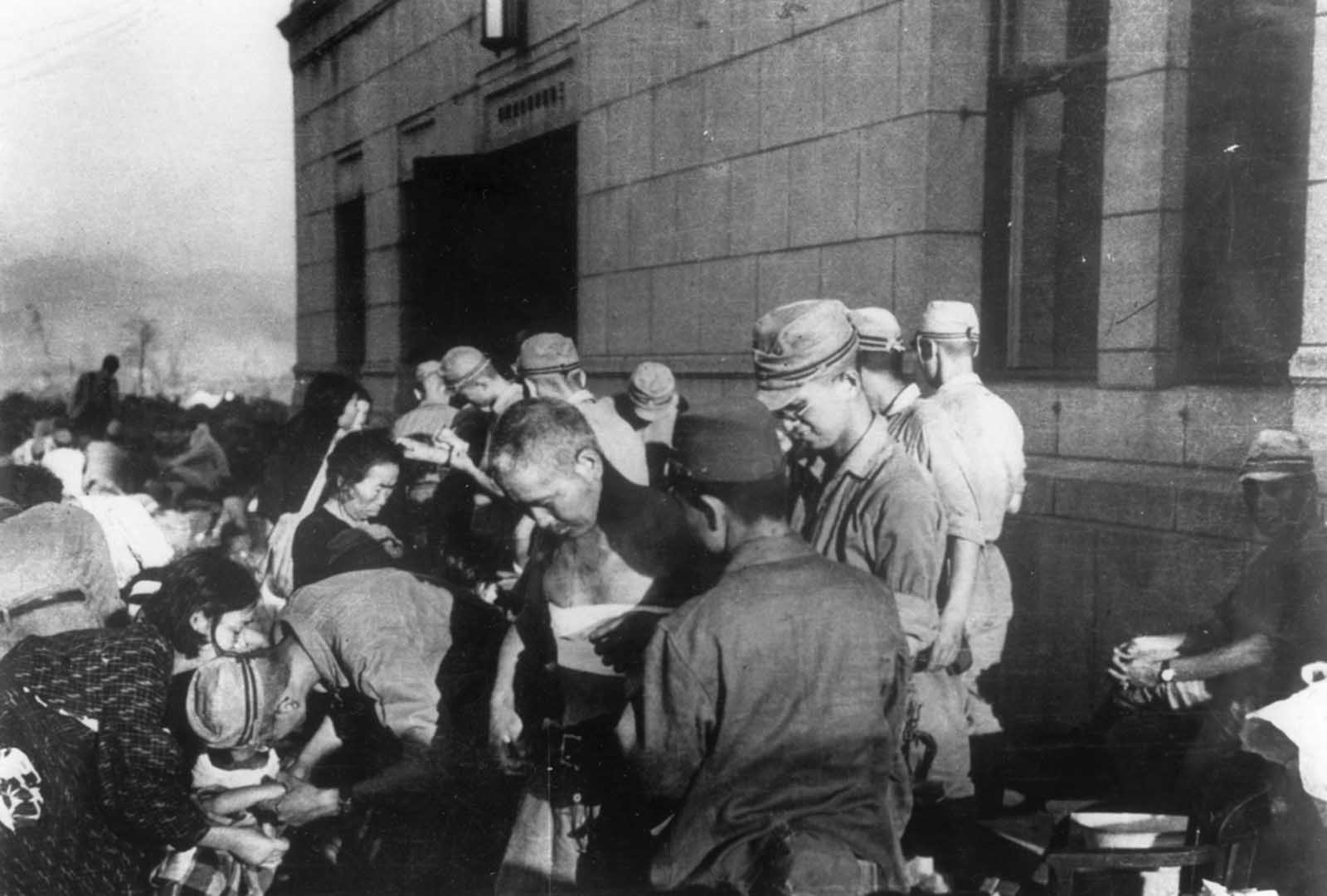 Shortly after the atomic bomb was dropped over the Japanese city of Hiroshima, survivors receive emergency treatment from military medics on August 6, 1945.