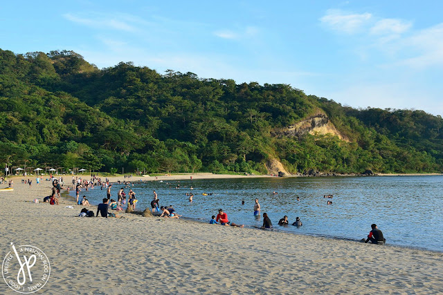 beach, mountains, shoreline, people sitting at the sand, people swimming