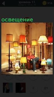 В комнате стоит множество торшеров, которые освещают мужчине в кресле