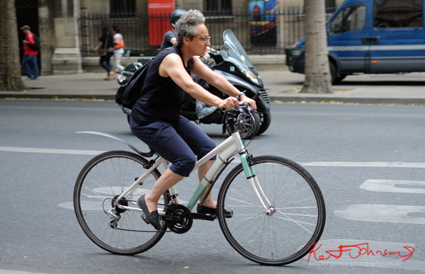 Woman on mountain bike wearing black singlet and navy plus four pants. Paris photos by Kent Johnson for Street Fashion Sydney.