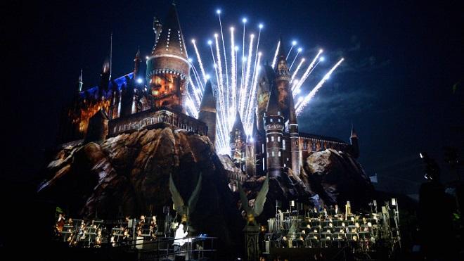 Imagem noturna da Orquestra Filarmônica de Los Angeles tocando em frente ao Castelo de Hogwarts vividamente iluminado. Ao fundo, fogos de artifício.