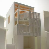 木製のスクリーンとバルコニーのある狭小都市型住宅