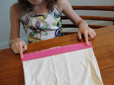 child cutting t-shirts to make dog toy