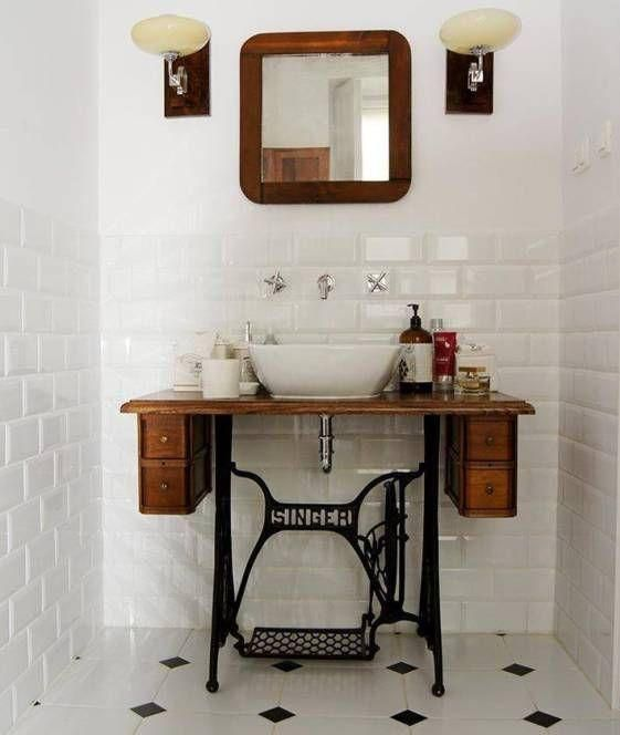 Gabinete e  pé de máquina de costura funciona como apoio para a cuba neste banheiro
