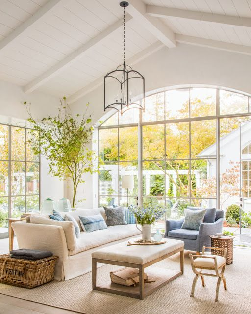 A stunning modern farmhouse style family room with steel windows, Belgian linen, and blue and white