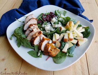 square plate with greens, smoked chicken, apples, cheese and more