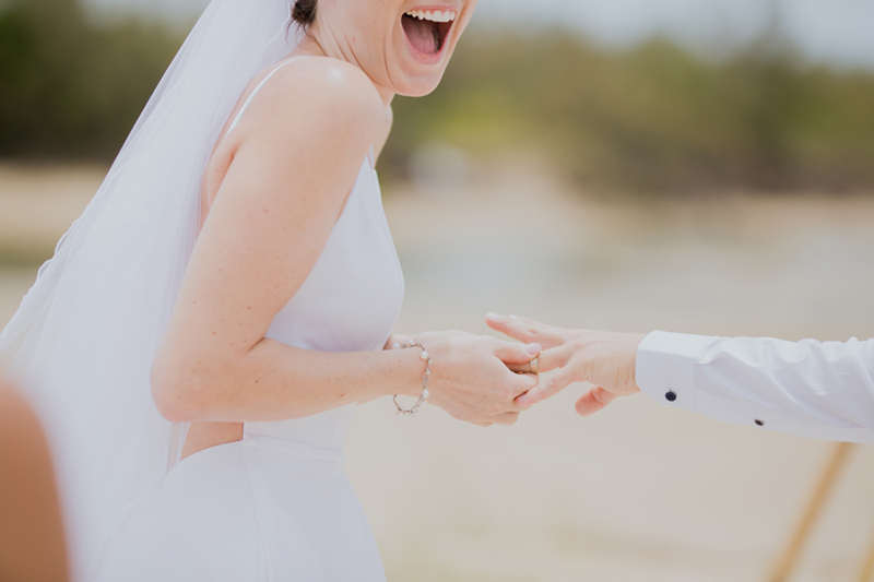 bride laughing at groom wedding ring stuck