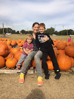 parent and two children in pumpkin patch; bio family picture for Beth Ringel