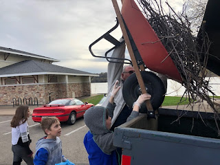 a child in a hoodie and an adult lift a red wheelbarrow up over the bed of a pickup to dump out sticks and brush.  Two other kids are in the background.
