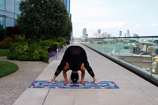 woman doing prasarita pose on a yoga mat outdoors