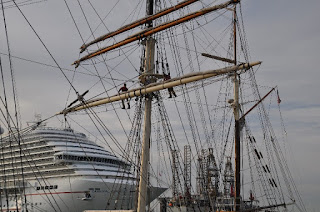 cruise ship passing behind a tall ship that has men in the rigging