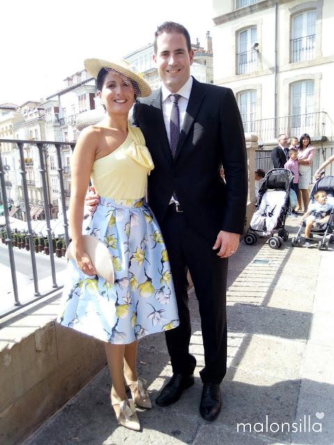 Invitada boda con su pareja, llevando una falda estampada, sombrero de paja con flores y bolso abanico de rafia color natural by malonsilla