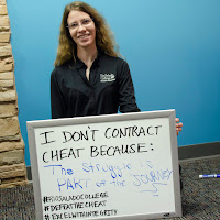 photo of a student holding up white board with her statement, I don't cheat because the struggle is part of the journey