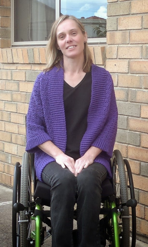 Front view of Jodie wearing cardigan while seated in manual wheelchair. The cardigan is long enough to be secured by sitting on it and tucking it into the chair's skirt guards. This prevents the cardigan from flapping about and getting caught in moving parts.