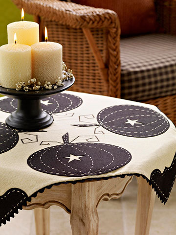 Decorate your home for fall with candles and this fun pumpkin tablecloth.
