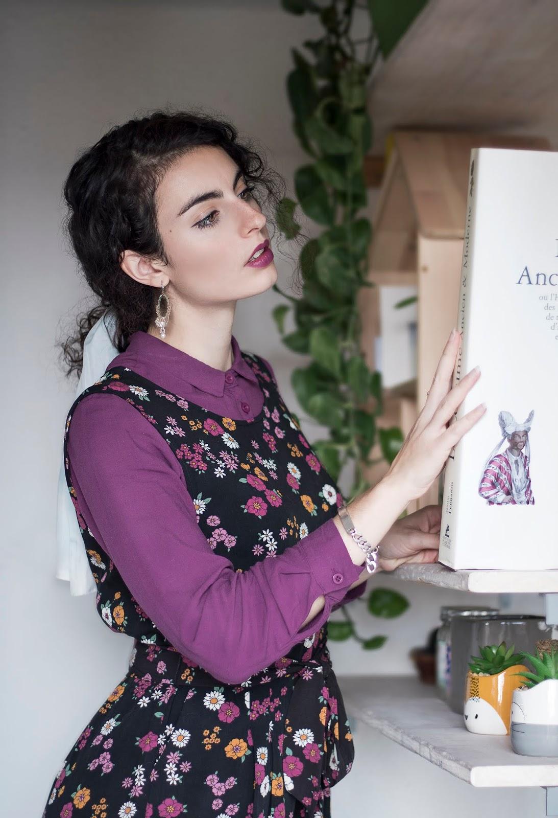Combinaison à fleurs, blouse violette, foulard dans les cheveu et chaussures jaunes.