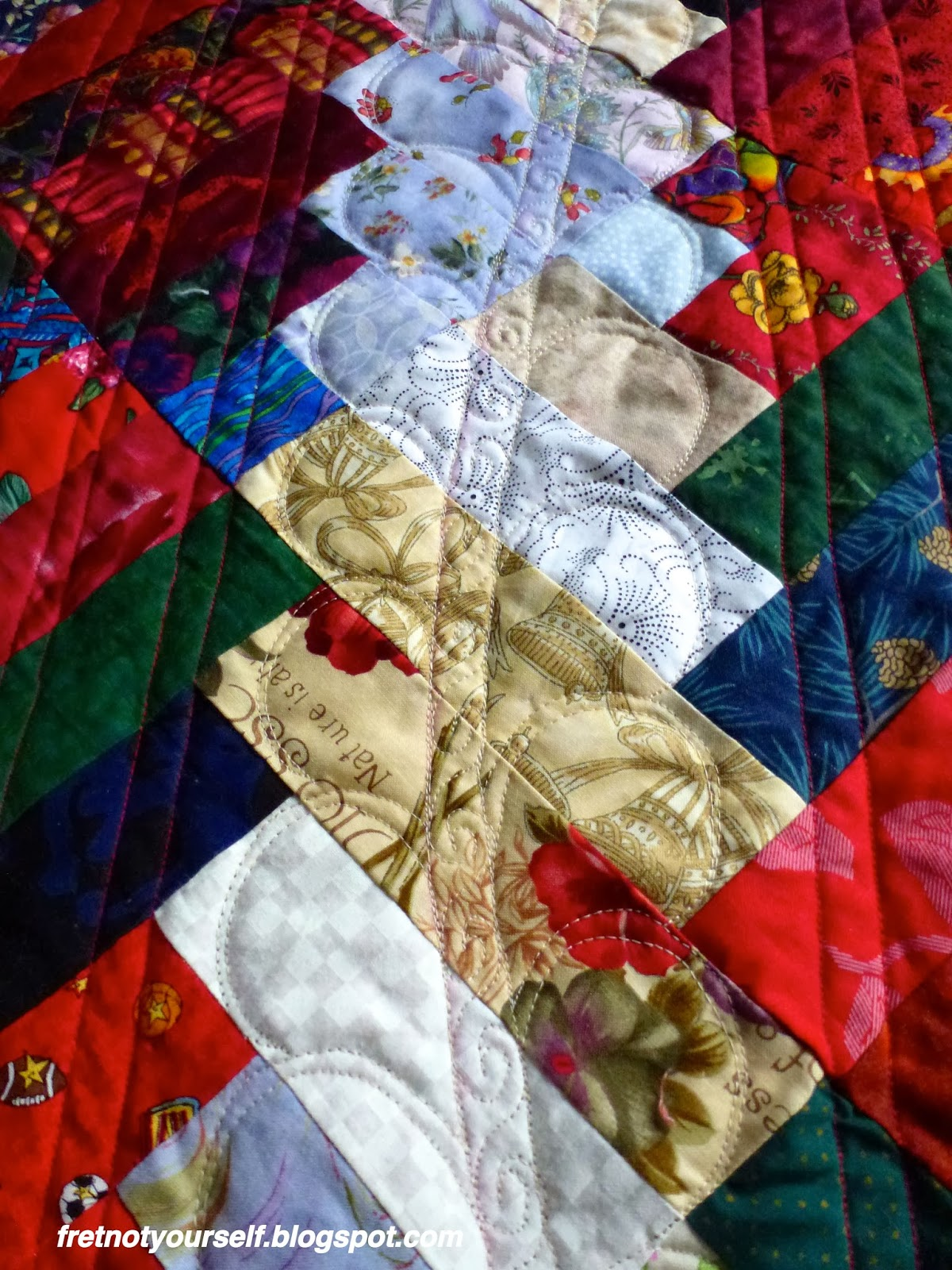 The quilting is a simplified feather of gentle c-shapes surrounding a stem filled with spirals.