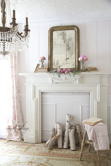 French style office with antique mantel with peonies and gold mirror