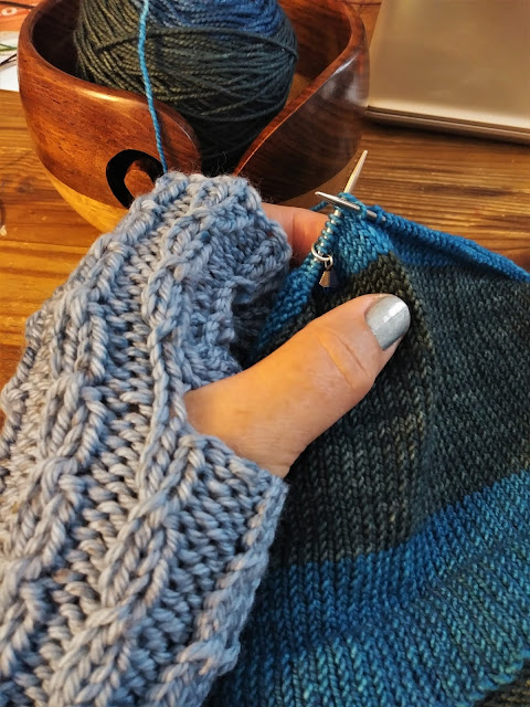 Warm fingerless gloves knit with an easy cable stitch and a blue hat knit with self striping washable wool yarn