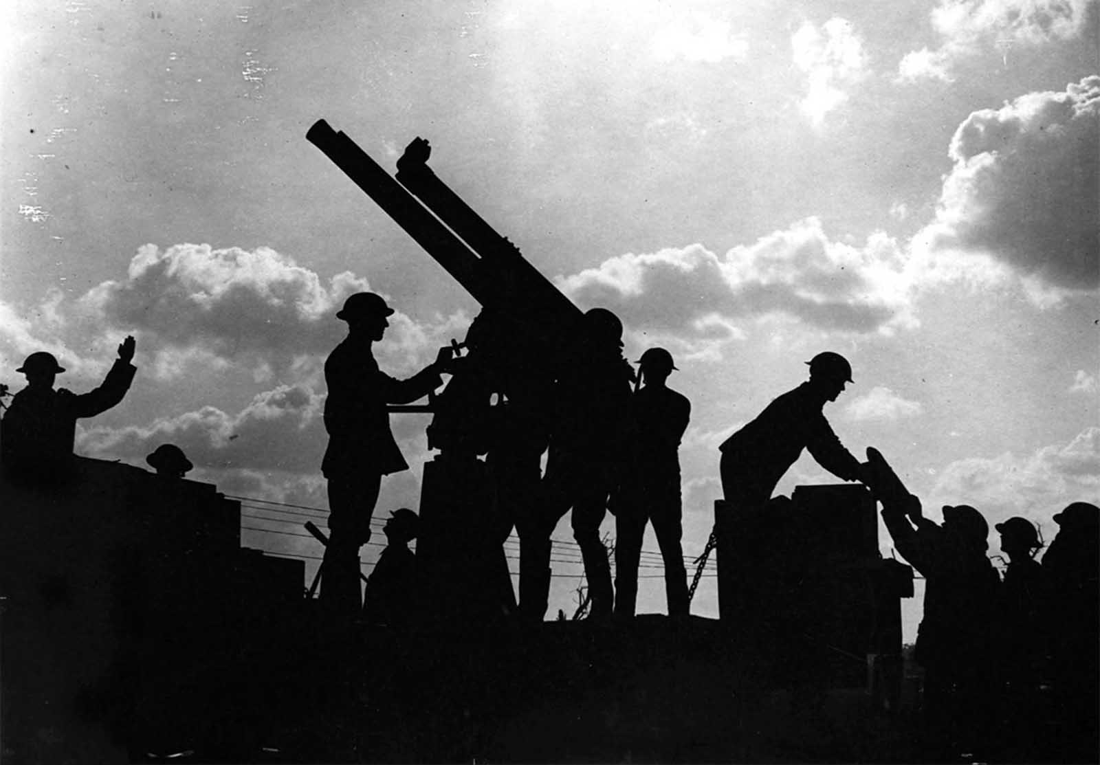 Soldiers silhouetted against the sky prepare to fire an anti-aircraft gun. On the right of the photograph a soldier is being handed a large shell for the gun. The Battle of Broodseinde (October 1917) was part of a larger offensive - the third Battle of Ypres - engineered by Sir Douglas Haig to capture the Passchendaele ridge.