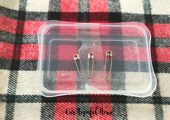 three silver safety pins red plaid flannel