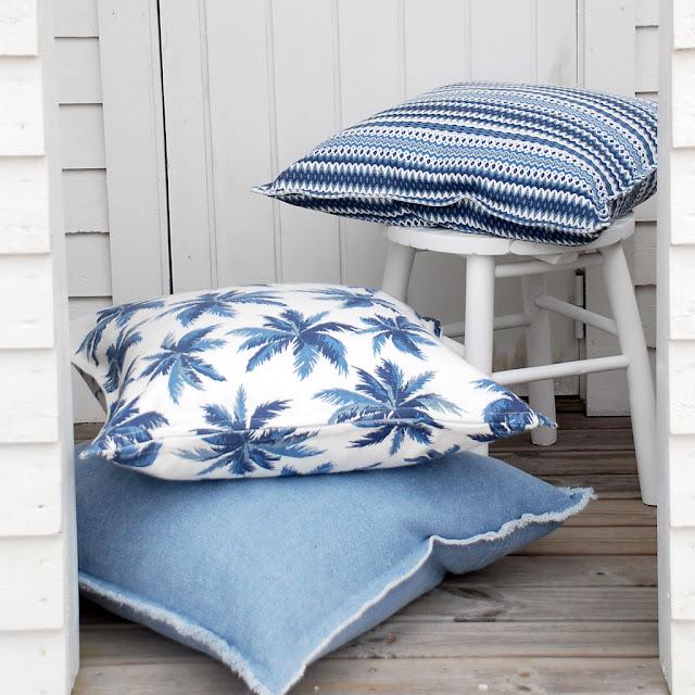 Vit kudde med blåa palmer.