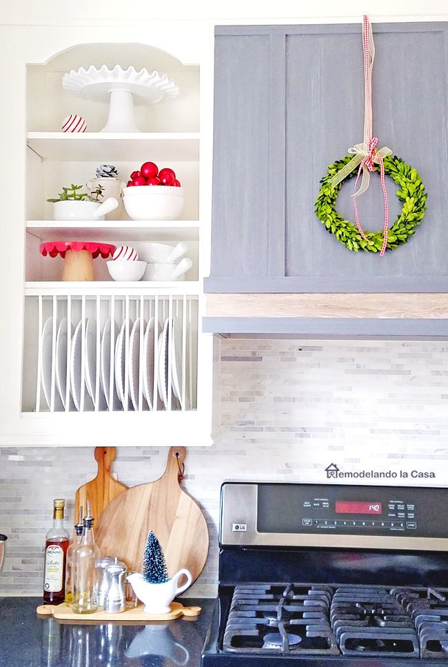small red touches of Christmas cheer in the cupboards and boxwood wreath on the range hood