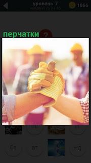 Рукопожатие в перчатках и в касках двух строителей на стройке