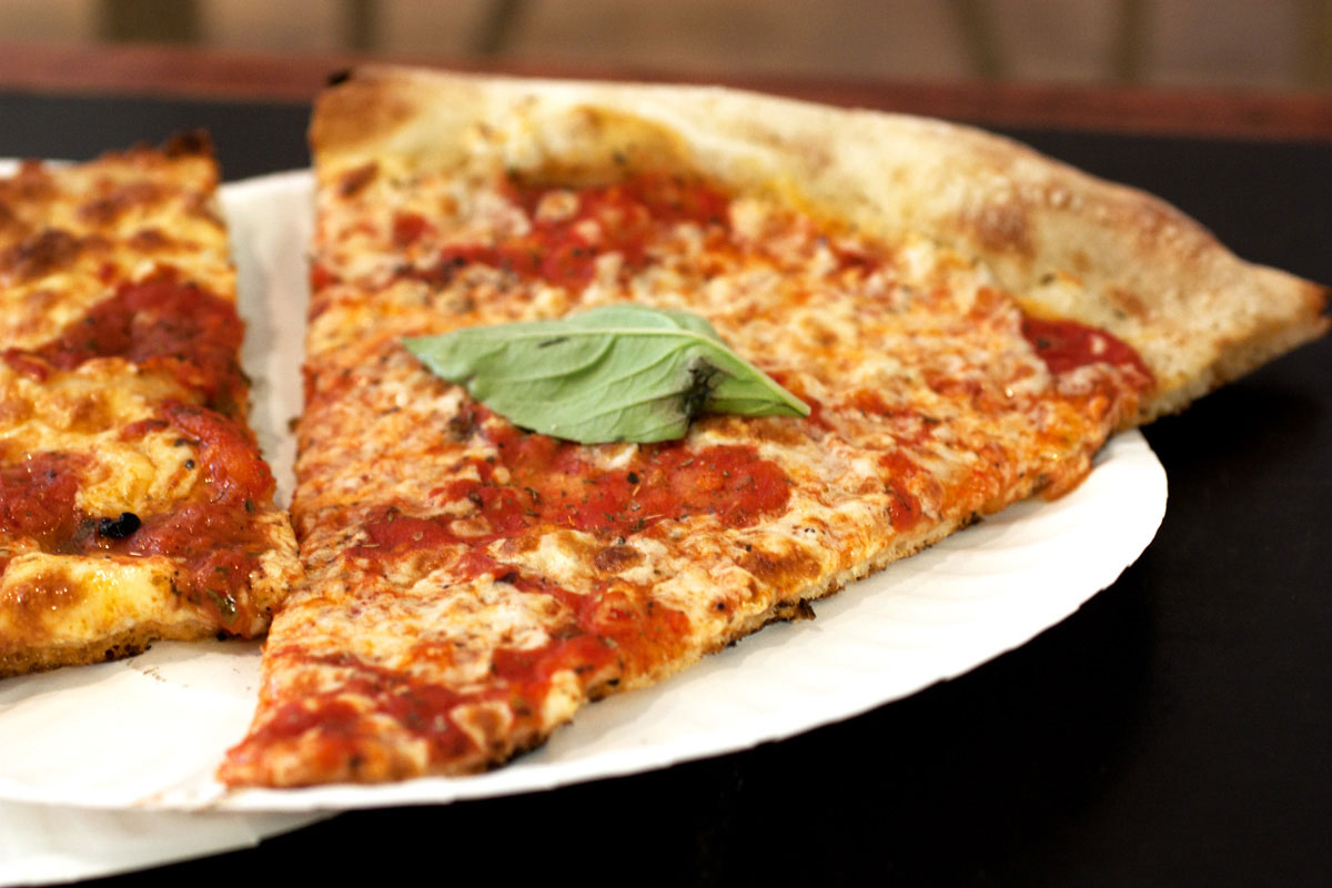 Herkullinen pala pizzaa, jossa tomaattikastiketta, juustoa ja päällä basilikan lehti.