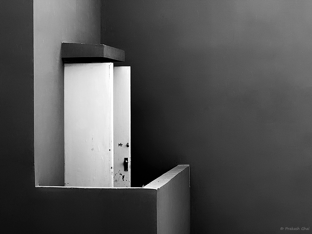 A Black and White Minimalist Photo of the open white door in the balcony, at Jawahar Kala Kendra Jaipur.
