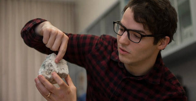 UC graduate student Andrew Gangidine holds a piece of Yellowstone silica containing bacterial life like the kind scientists may one day find on Mars.