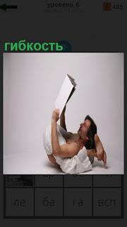 На полу, показывая свою гибкость, мужчина читает журнал